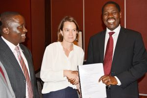 Global Communities Country Director Kimberly Tilock handing over a copy of the draft County Cooperatives Model Bill to the COG Chair,Peter Munya