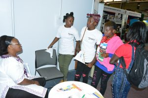 Luciana of Global Communities talking to some girls who visited the booth to learn about USAID/DREAMS program